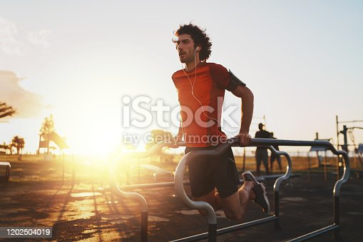 Handsome male athlete exercising on parallel bars in the park