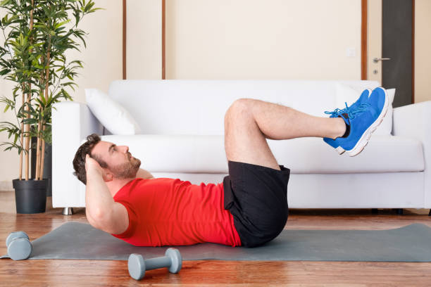 Athletic young man doing curl ups exercise at home stock photo