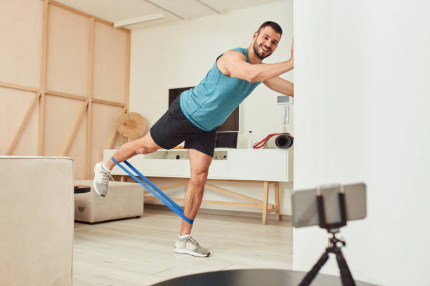 Athletic young man doing exercise with elastic resistance band stock photo