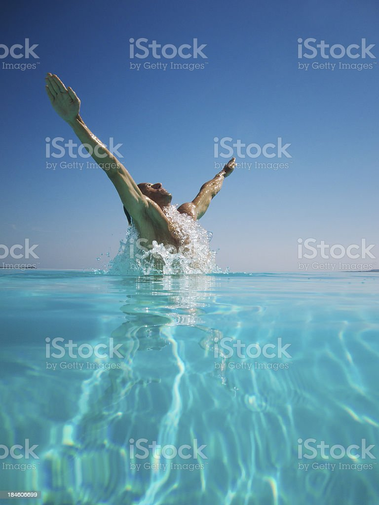 Athletic Young Man Emerging From Turquoise Swimming Pool Arms Spread stock photo