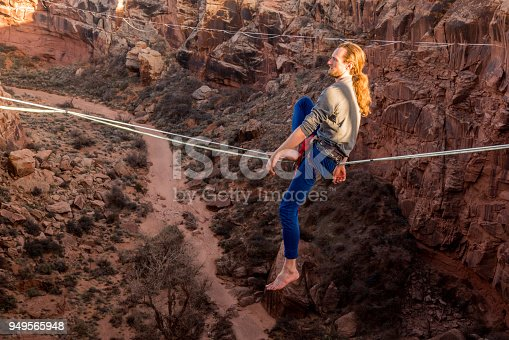 Young male extreme athlete on doing highlining or slacklining across a deep canyon near Moab Utah