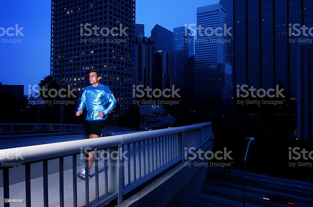 Athletic Young Man Running Across Bridge at Dusk royalty-free stock photo