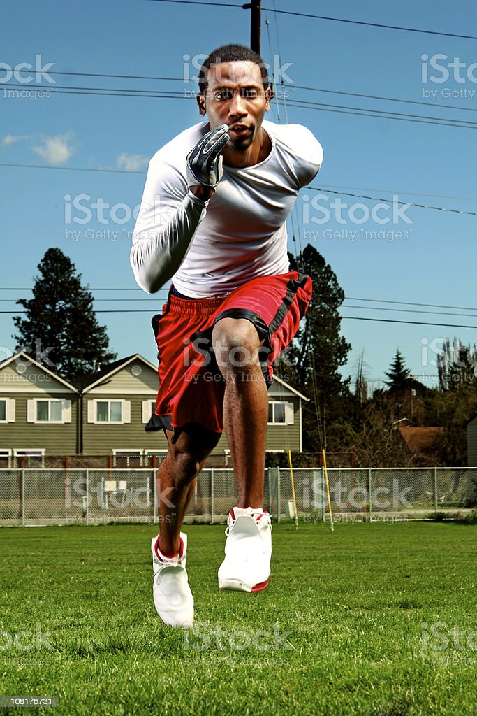 Athletic Young Man Running and Training in Football Field royalty-free stock photo