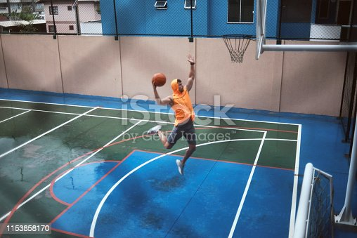 young man playing basketball on a rainy day