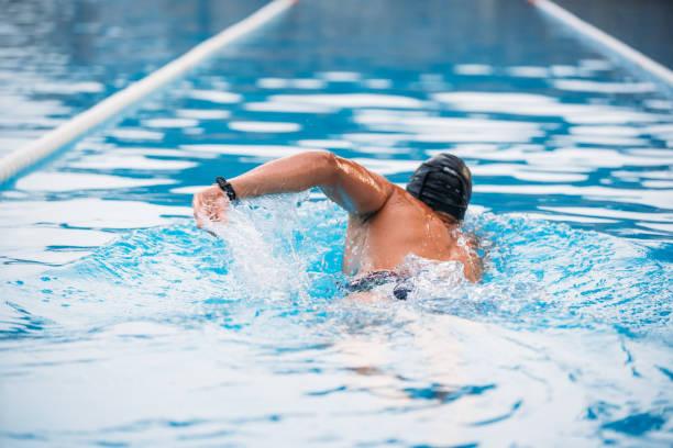joven atlético nadando por la espalda en una piscina. competición de natación. - vuelta completa fotografías e imágenes de stock