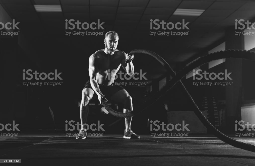 Athletic young man with battle rope doing exercise in the fitness gym. stock photo