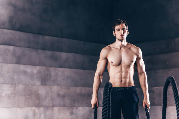 Athletic young man with battle rope doing exercise. stock photo