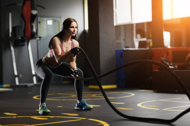 Athletic young woman doing gym exercises with a rope. stock photo
