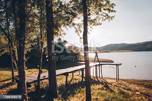 Athletic young and beautiful woman exercising Yoga on a wooden pier next to a mountain lake in the morning. Training and enjoy the new day