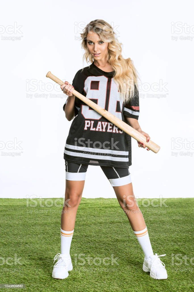 athletic young woman in sportswear standing on grass with baseball bat isolated on white stock photo