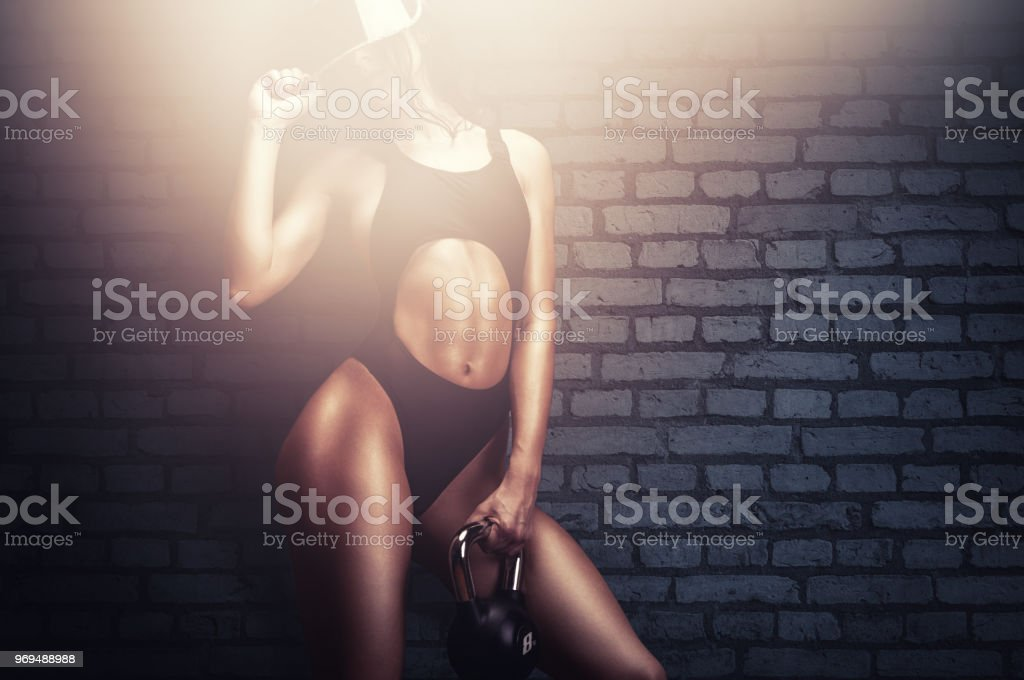 Athletic young woman in training posing with kettle bell after workout stock photo
