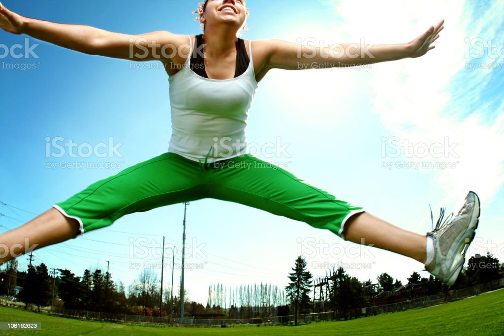 Athletic Young Woman Jumping and Exercising Outside royalty-free stock photo