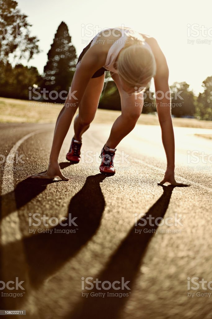 Athletic Young Woman on Track About to Run royalty-free stock photo