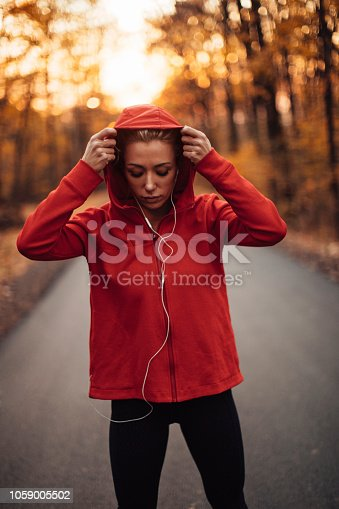 Athletic young woman outdoors in the park in Fall putting the hoodie on