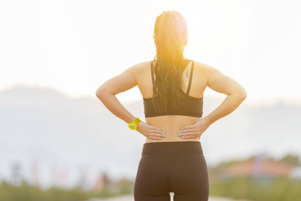 athletic young woman rubbing muscles of lower back after jogging - low section stock photos and pictures