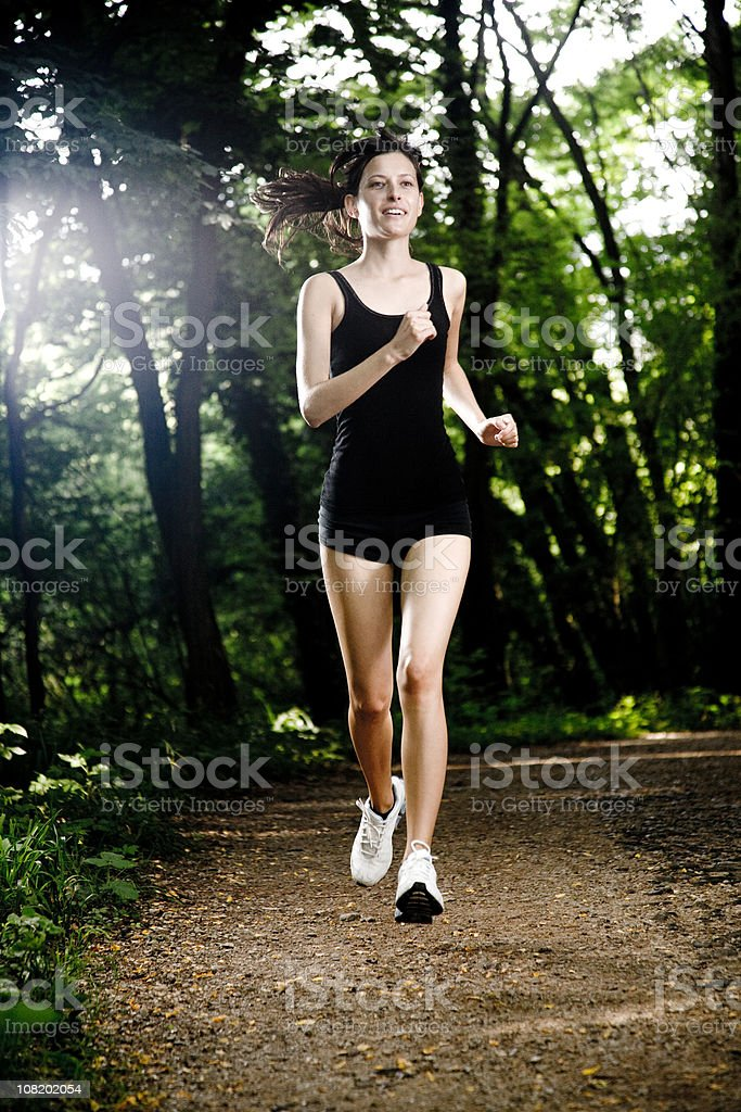 Athletic Young Woman Running Along Path in Forest royalty-free stock photo