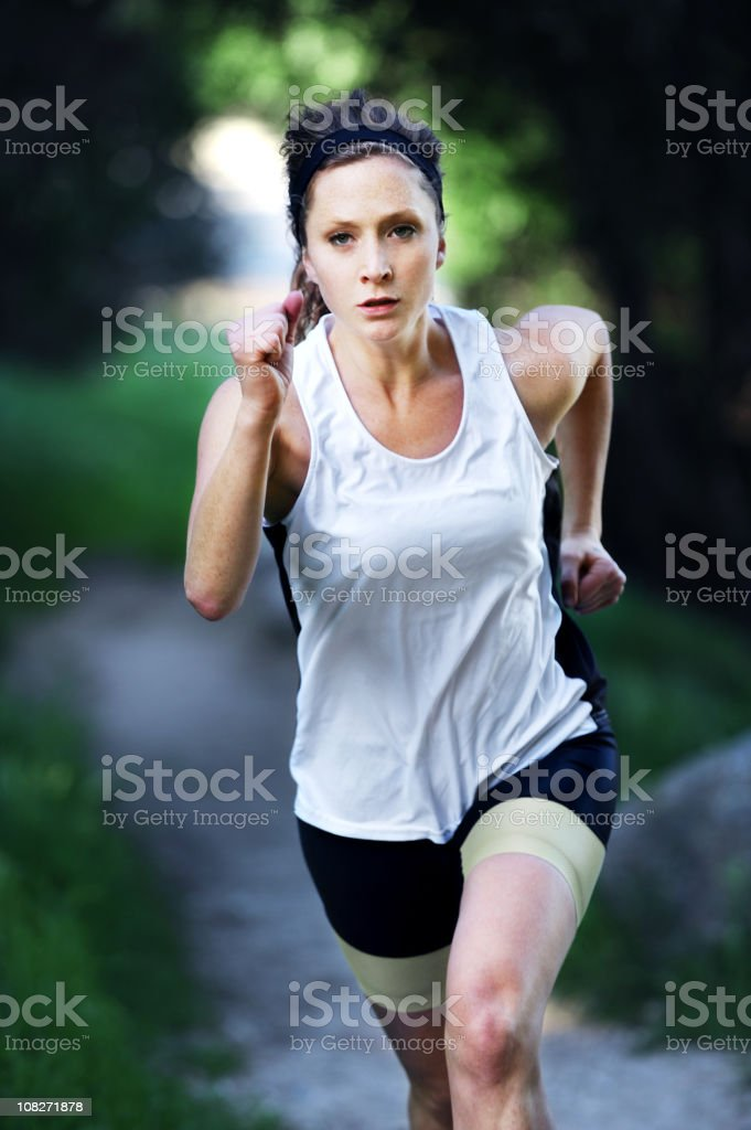 Athletic Young Woman Running on Trail Outside royalty-free stock photo