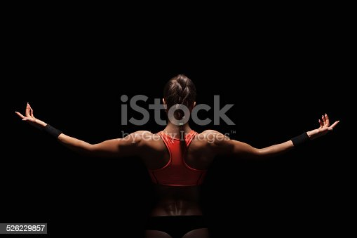 istock Athletic young woman showing muscles of the back 526229857