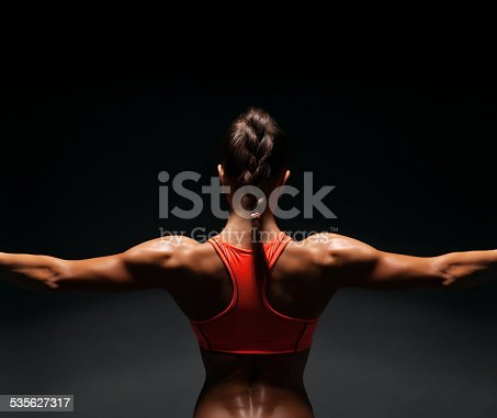 istock Athletic young woman showing muscles of the back 535627317