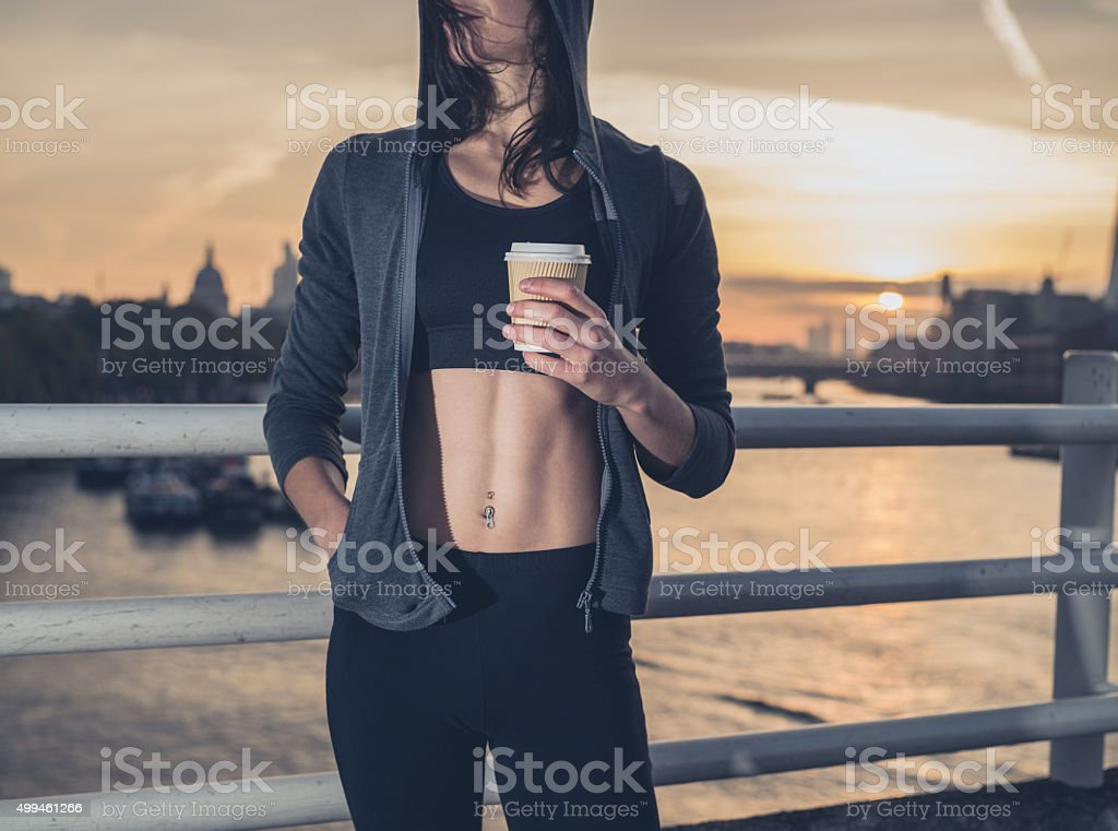 Athletic young woman with cup in London at sunrise An athletic young woman with toned abs  is standing on a bridge in London at sunrise with a paper cup in her hand 2015 Stock Photo