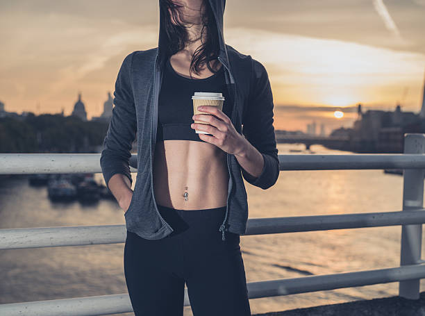 Athletic young woman with cup in London at sunrise stock photo