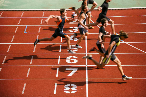 Athlets sprinting at finish line Sprint competition on running track. Finish line low angle view. win stock pictures, royalty-free photos & images