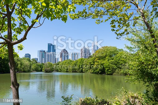Atlanta, USA - April 20, 2018: Cityscape skyline view in Piedmont Park in Georgia framing through trees of urban city skyscrapers downtown at Lake Clara Meer