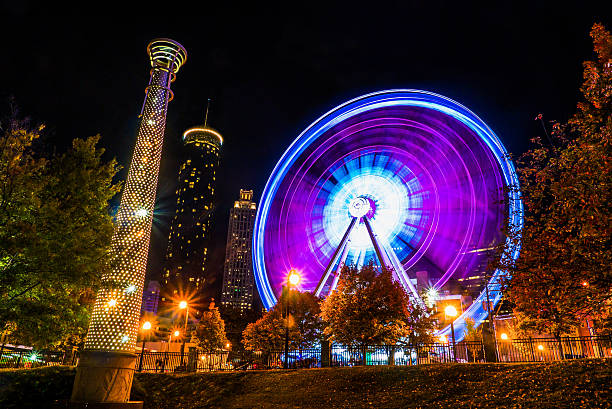 Atlanta downtown Ferris Wheel in motion lit up at night The Sky View Ferris Wheel in Downtown Atlanta, taken from Centennial Olympic Park at night, using a long exposure to capture the blurred motion of the ferris wheel lights. ferris wheel stock pictures, royalty-free photos & images