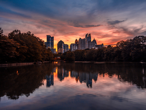 Sunset view of midtown Atlanta overlooking Lake Clara Meer, with watery reflection of the city skyline and trees