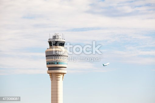 The air traffic control tower at Atlanta's Hartsfield-Jackson International Airport (ATL) with a plane taking off to the right. This airport is the world's busiest and this tower handles nearly one million planes each year. Two other airplanes are semi-visible in the sky, but very small.