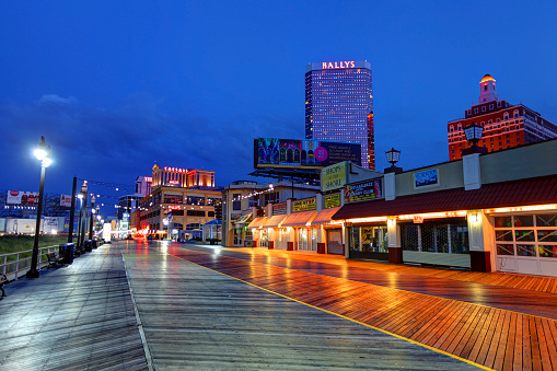 The Atlantic City casinos and Boardwalk along the oceanfront at night. Atlantic City located on the Jersey shore is a resort city on Absecon Island  in Atlantic County, New Jersey. Atlantic City is known for its two mile long boardwalk, gambling casinos, great nightlife, beautiful beaches, and the Miss America Pageant.