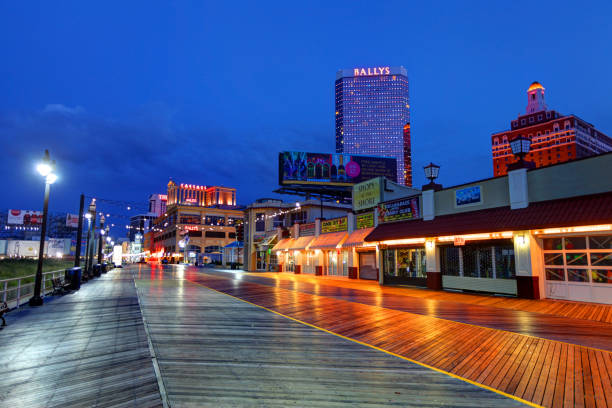 Atlantic City Boardwalk The Atlantic City casinos and Boardwalk along the oceanfront at night. Atlantic City located on the Jersey shore is a resort city on Absecon Island  in Atlantic County, New Jersey. Atlantic City is known for its two mile long boardwalk, gambling casinos, great nightlife, beautiful beaches, and the Miss America Pageant. boardwalk stock pictures, royalty-free photos & images