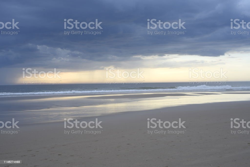 Silver and gold clouds with waves under the rain at sunset. View from...
