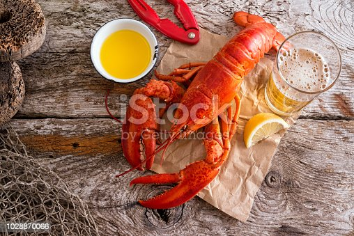 A delicious cooked atlantic lobster with melted butter, beer and lemon on a rustic wood background.