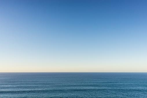 A calm Atlantic ocean and clear evening sky.