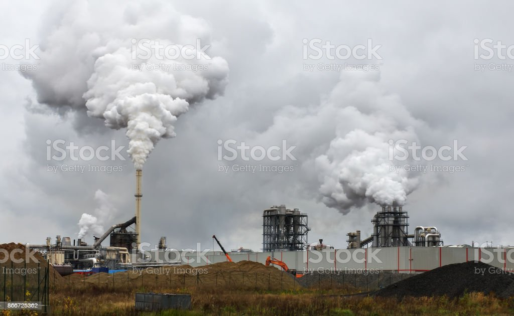 Atmospheric Air Pollution From Industrial Smoke Now. Pipes Steel Plant. Thick Smoke and Steam of MDF Production. Works in Cloudy Rainy Day. Environmental pollution. stock photo