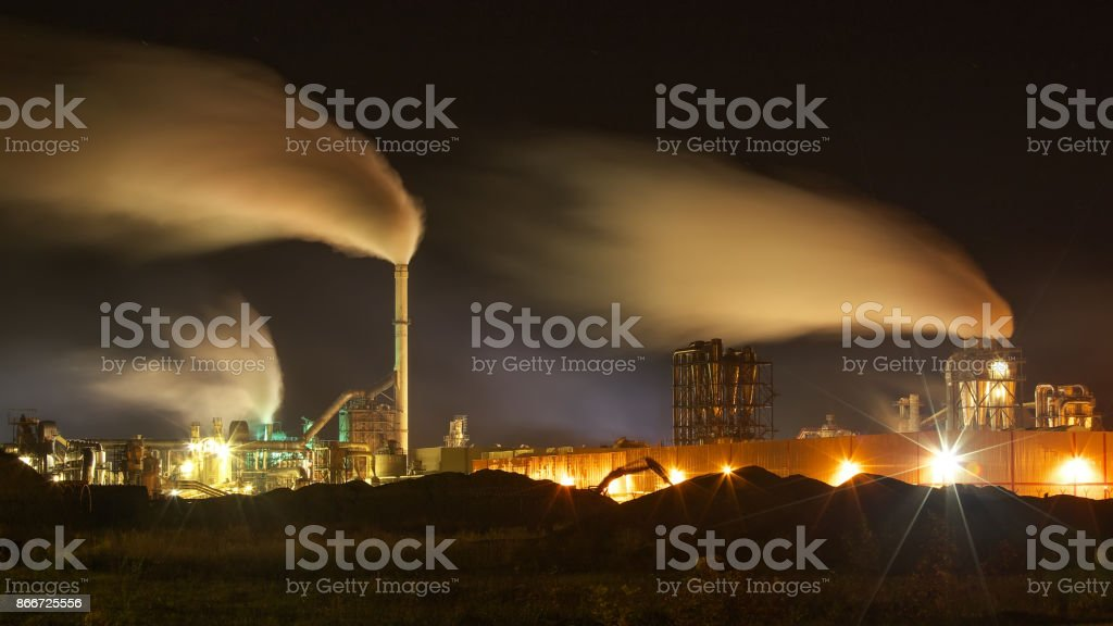 Atmospheric Air Pollution From Industrial Smoke Now. Pipes Steel Plant. Thick Smoke and Steam of MDF Production. Works in Cloudy Day at night. Environmental pollution. Slow shutter speeds stock photo