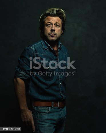 Atmospheric dark studio portrait of a tough middle-aged man with blonde hair in a jeans shirt.