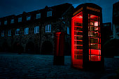 Atmospheric image of telephone box or phone booth in the street with historical architecture at night in London, England, UK