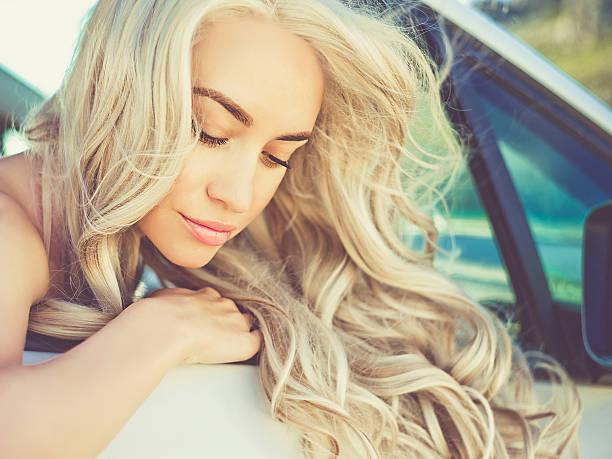 atmospheric portrait of beautiful blonde in car - soup_studio stock-fotos und bilder