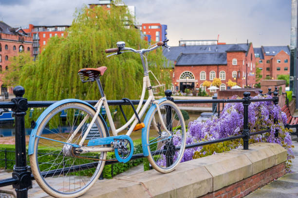 Atmospheric scene  of a parked bicycle at the restored Victorian canal system in Castlefield area of Manchester stock photo