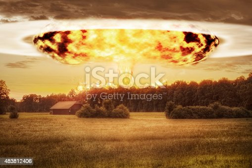 Atomic bomb detonated in the distance seen over an idlyllic rural landscape in Europe.