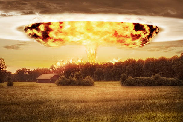 Atomic Bomb and Mushroom Cloud over Rural Landscape Atomic bomb detonated in the distance seen over an idlyllic rural landscape in Europe. davelongmedia stock pictures, royalty-free photos & images