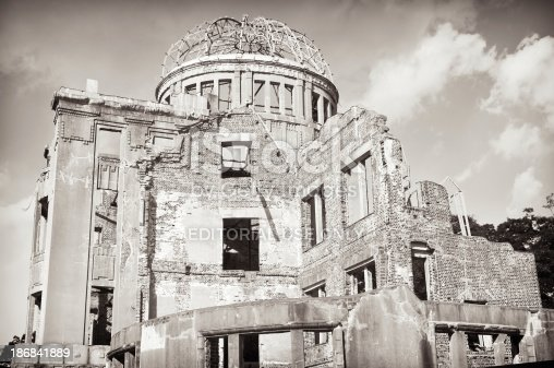 Black and white image of the Atomic Bomb Dome building in Hiroshima, Japan.  The building was very close to the detonation position of the nuclear bomb which fell on the city on 6th August, 1945.  It has been intentionally left in an unrepaired state since then.
