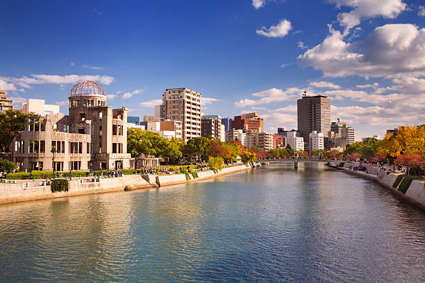 Atomic Bomb Dome in Hiroshima, Japan The Atomic Bomb Dome on the left and the Peace Memorial Park on the right along the river in Hiroshima on a sunny afternoon in autumn. hiroshima prefecture stock pictures, royalty-free photos & images