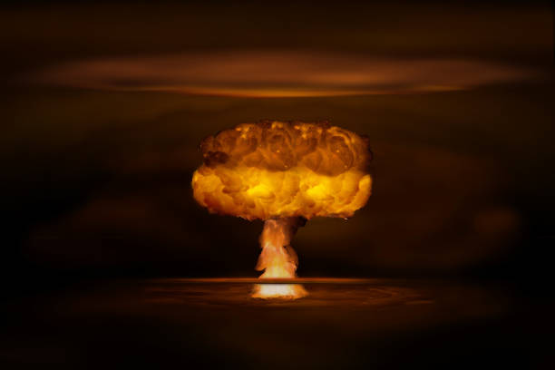 Atomic bomb realistic explosion, orange color with smoke on black background stock photo