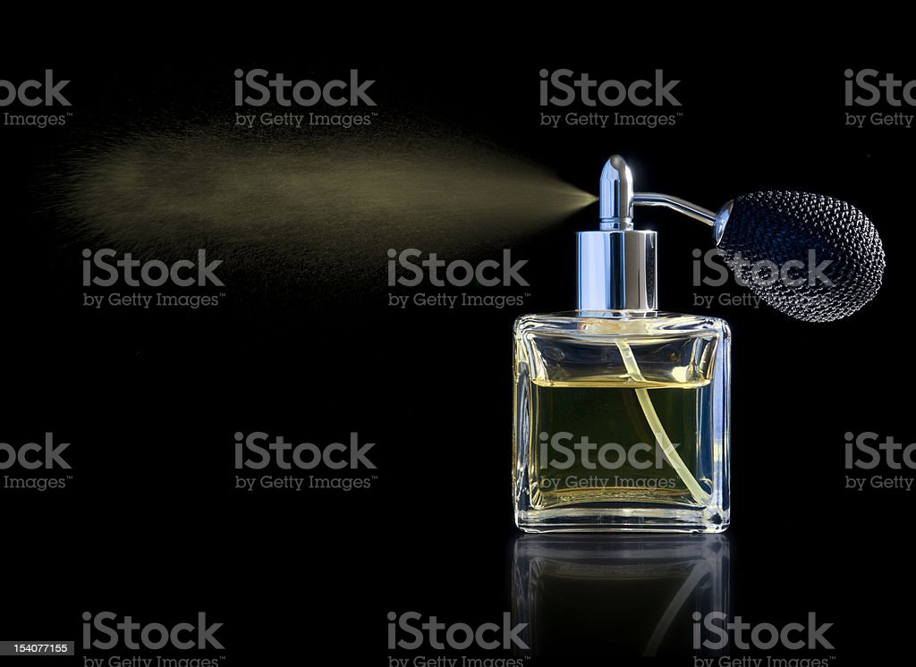 Atomiser spraying perfume from glass bottle stock photo