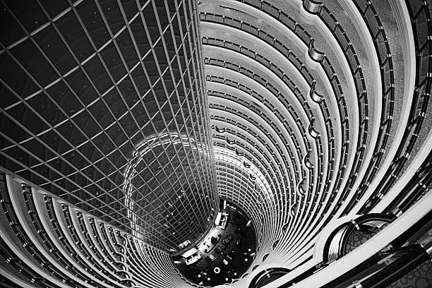 Atrium inside Jin Mao Tower in Shanghai, China View down from the public observation deck at the 88th floor of Jin Mao tower into the 115 m high barrel-vaulted atrium of a hotel. jin mao tower stock pictures, royalty-free photos & images