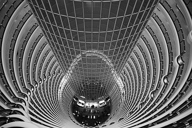 Atrium inside Jin Mao Tower, Shanghai, China View down from the public observation deck at the 88th floor of Jin Mao tower into the 115 m high barrel-vaulted atrium of a hotel jin mao tower stock pictures, royalty-free photos & images