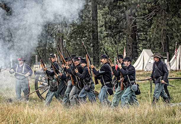 Attack Portola, California, United States-July 4, 2015: Members of the 72nd reenactor's group advance towards the Confederate lines during a Civil War reenactment. american civil war stock pictures, royalty-free photos & images
